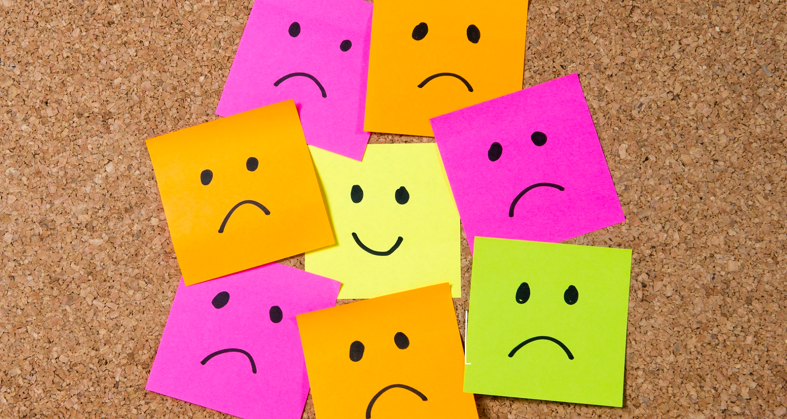 smiley post it note on corkboard happiness versus depression concept